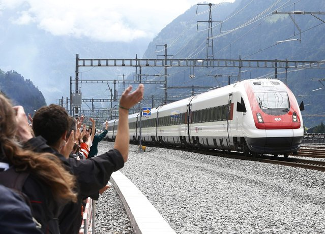 Guests waves at a train that has crossed the tunnel during the opening ceremony of the NEAT Gotthard Base Tunnel, the world's longest and deepest rail tunnel, near the town of Erstfeld, Switzerland June 1, 2016. (Photo by Arnd Wiegmann/Reuters)