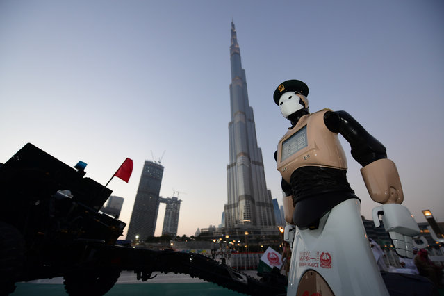 The world's first operational police robot stands at attention as they prepare a military cannon to fire to mark sunset and the end of the fasting day for Muslims observing Ramadan, in Downtown Dubai on May 31, 2017. (Photo by Giuseppe Cacace/AFP Photo)