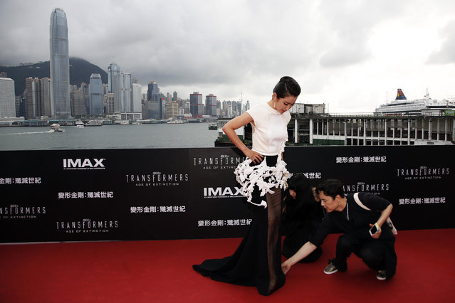 "Assistants help to arrange the dress of Chinese actress Li Bingbing on the red carpet as she arrives for the world premiere of the film ""Transformers: Age of Extinction"" in Hong Kong June 19, 2014. (Photo by Tyrone Siu/Reuters)"