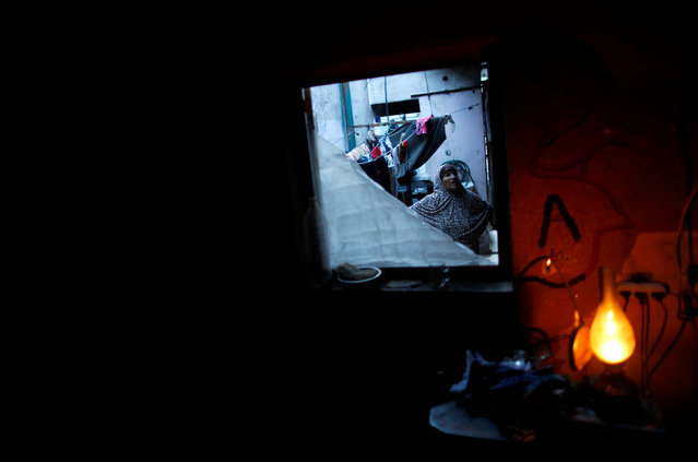 A Palestinian woman stands in her house as a kerosene lamp lightens a dark room during a power cut in Beit Lahiya town in the northern Gaza Strip May 2, 2016. (Photo by Mohammed Salem/Reuters)