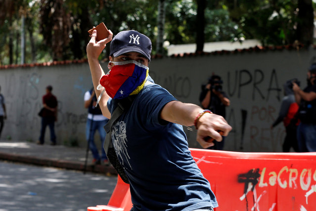 A demonstrator attempts to throw a stone towards riot police officers during a protest called by university students against Venezuela's government in Caracas, Venezuela, June 9, 2016. (Photo by Carlos Garcia Rawlins/Reuters)
