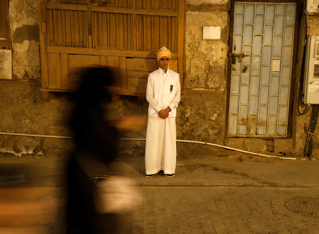 A woman walks past a boy wearing a traditional costume during the holy fasting month of Ramadan at Jeddah's historical area Al-Balad, Saudi Arabia June 9, 2016. (Photo by Faisal Al Nasser/Reuters)