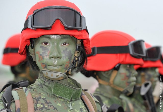 A group of Taiwanese women paratroops pose for photos after a drill held at Taiwan's northern Hsinchu airbase. Taiwan tested its ability to defend one of its largest air bases against Chinese invasion