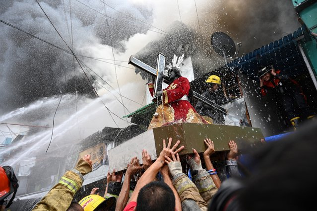 Residents and firefighters carry a Black Nazarene statue from a burning house after a fire hit an informal settlement in Manila on October 22, 2019. (Photo by Ted Aljibe/AFP Photo)