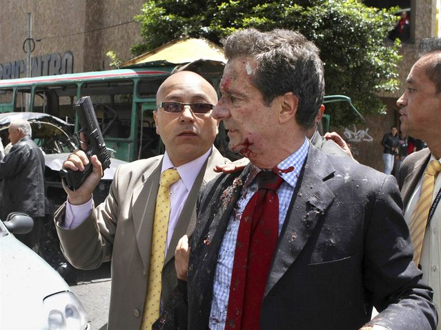 Former Colombian Interior Minister Fernando Londono is accompanied by a bodyguard after being injured in an explosion in a central avenue in Bogota on May 15, 2012