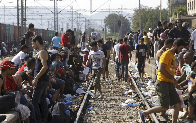 Migrants sit alongside railway tracks while waiting for a train towards Serbia, at the railway station in the southern Macedonian town of Gevgelija, Wednesday, August 12, 2015. Macedonia is seeing increasing numbers of migrants flow through its southern and northern borders with Greece and Serbia as thousands transit through the country on their way from the Middle East, Asia and Africa. (Photo by Boris Grdanoski/AP Photo)