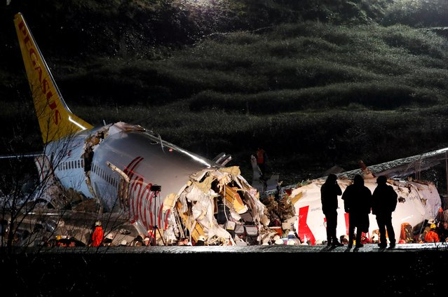 Police officers inspect the Pegasus Airlines Boeing 737-86J plane, that overran the runway during landing and crashed, at Istanbul's Sabiha Gokcen airport, Turkey February 5, 2020. The plane carrying 171 passengers from the Aegean port city of Izmir split into three after landing in rough weather. Officials said no-one had lost their lives in the accident, but dozens of people were injured. (Photo by Murad Sezer/Reuters)