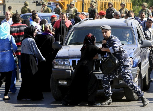 A woman trying to close the road clashes with a Lebanese security officer during a protest against the detention of Sheikh Ahmed al-Assir by Lebanese authorities, in Sidon, south Lebanon August 15, 2015. Lebanese authorities detained the hardline Sunni Islamist cleric wanted for attacks on the Lebanese army as he tried to flee the country on Saturday, security officials said. (Photo by Ali Hashisho/Reuters)