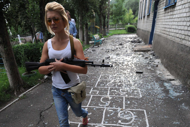 Pro-Russian militants patrol in a kindergarten after bombardments carried out by Ukrainian armed forces  in Petrovsky 25 kilometres west of Donetsk, on July 15, 2014. (Photo by Dominique Faget/AFP Photo)