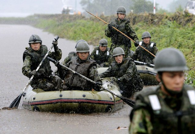 Japan's Ground Self-Defense Force personnel search for missing people in Aso, Kumamoto Prefecture on July 14, 2012