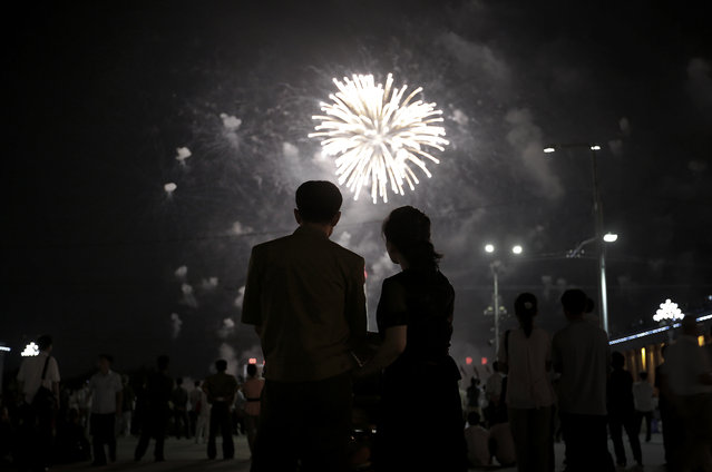 A North Korean couple is silhouetted against a fireworks explosion, Sunday, July 27, 2014 in central Pyongyang, North Korea. North Koreans gathered at Kim Il Sung Square to watch a fireworks display as part of celebrations for the 61st anniversary of the armistice that ended the Korean War. (Photo by Wong Maye-E/AP Photo)