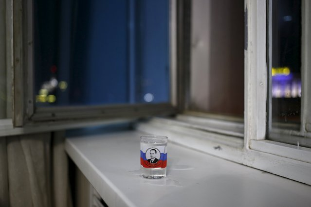A vodka glass with a picture of Russian President Vladimir Putin is seen in this photo illustration taken in a hotel room in Kazan, Russia, July 31, 2015. He may be in charge of an economy in crisis, but if mobile phone covers and souvenir mugs are a barometer of popularity, Russian President Vladimir Putin need not fear for his political future. (Photo by Stefan Wermuth/Reuters)
