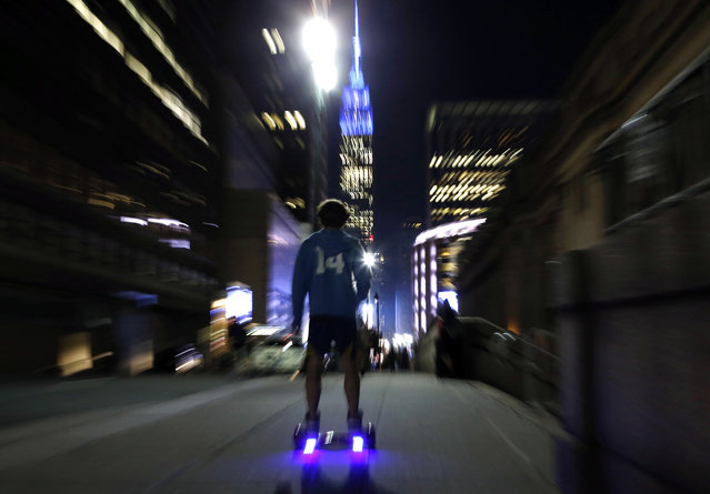 In this October 21, 2015, file photo, a young man rides a hoverboard along a Manhattan street toward the Empire State Building in New York. More than 500,000 hoverboards are being recalled after reports that they can burst into flames. The Consumer Product Safety Commission said Wednesday, July 6, 2016, it has received 99 reports of battery packs in the two-wheel motorized scooters catching fire or exploding that causing burns or property damage. The recalled hoverboards were made by eight companies. (Photo by Kathy Willens/AP Photo)