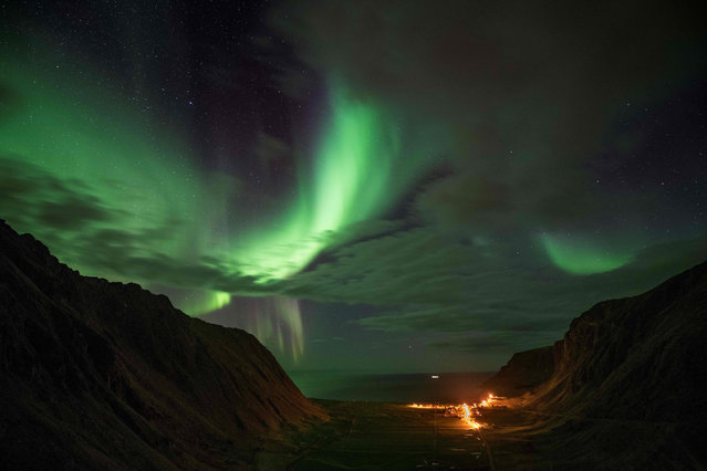 Northern lights (Aurora borealis) are photographed on Unstad's bay in the arctic circle, on September 22, 2017, on the eve of the opening of the Lofoten Masters 2017, the world's most northerly surf competition. (Photo by Olivier Morin/AFP Photo)
