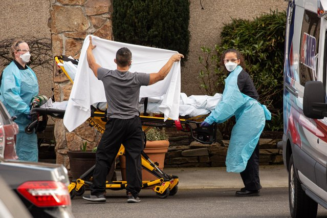 Healthcare workers transport a patient on a stretcher into an ambulance at Life Care Center of Kirkland in Kirkland, Washington on February 29, 2020. Dozens of staff and residents at Life Care Center of Kirkland are reportedly exhibiting coronavirus-like symptoms, with two confirmed cases associated with the nursing facility reported so far. (Photo by David Ryder/Getty Images)