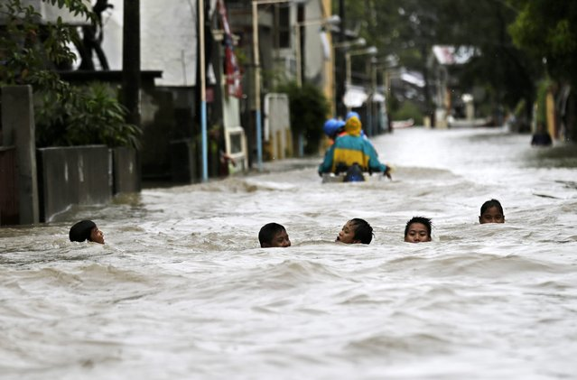 Children wade into water in the town of Hermosa in the Philippines on August 5, 2014, where heavy rainfall brought by Typhoon Halong caused widespread flooding. (Photo by Francis R. Malasig/EPA)