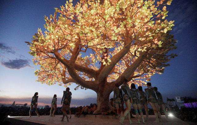 "Burning Man participants give a dance performance as the ""Playa Players Collective"" orchestra play Stravinsky's ""Rites of Spring"" in front of a huge art project called the ""Tree of Tenere"" created by a group of San Francisco artists in the middle of the open desert during the 3rd day of the 2017 Burning Man festival in the Black Rock Desert of Nevada, U.S. on August 30, 2017. (Photo by Jim Urquhart/Reuters/Splash News and Pictures)"