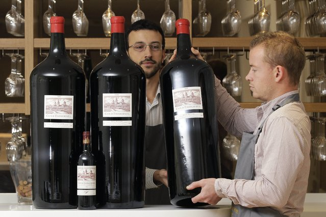 This is a Thursday, November 17, 2011 file photo of Antique Wine Company's employees poses with three Melchiors and a standard size bottle of Cos D'Estournel wine at the wine merchant in London, Thursday, November 17, 2011. A Melchior  holds 18 litres, 24 bottles or 102 glasses of wine. The free online dictionary of current usage, created by the publishers of the venerable Oxford English Dictionary, issued its quarterly update Thursday August 27, 2015. (Photo by Sang Tan/AP Photo)