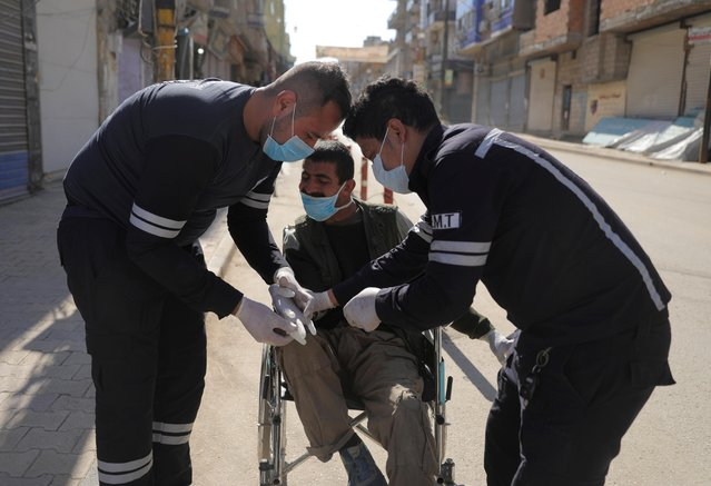 Health workers put gloves on a man in a wheelchair along an empty street, as restrictions are imposed as measure to prevent the spread of the coronavirus disease (COVID-19) in Qamishli, Syria on March 23, 2020. (Photo by Rodi Said/Reuters)