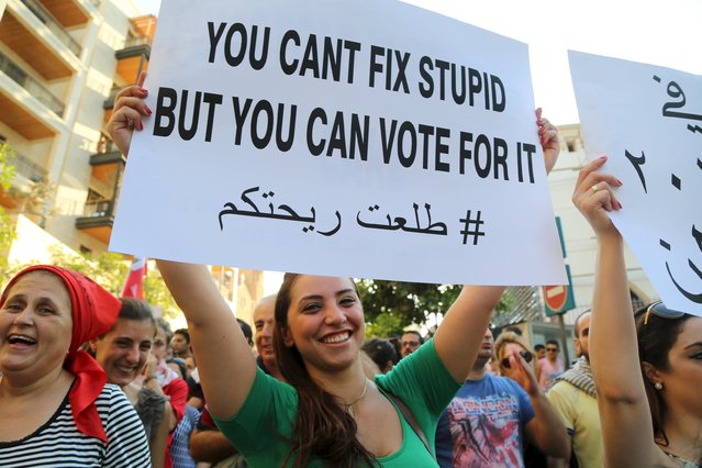 A protester holds up a placard during a protest against corruption and against the government's failure to resolve a crisis over rubbish disposal in Beirut, Lebanon August 29, 2015. Thousands of protesters waving Lebanese flags and chanting anti-government slogans converged on a square in central Beirut on Saturday for a rally against political leaders they say are incompetent and corrupt. (Photo by Aziz Taher/Reuters)