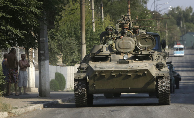 Pro-Russian rebels ride on an APC in the town of Krasnodon, eastern Ukraine, Sunday, August 17, 2014. A column of several dozen heavy vehicles, including tanks and at least one rocket launcher, rolled through rebel-held territory on Sunday. (Photo by Sergei Grits/AP Photo)