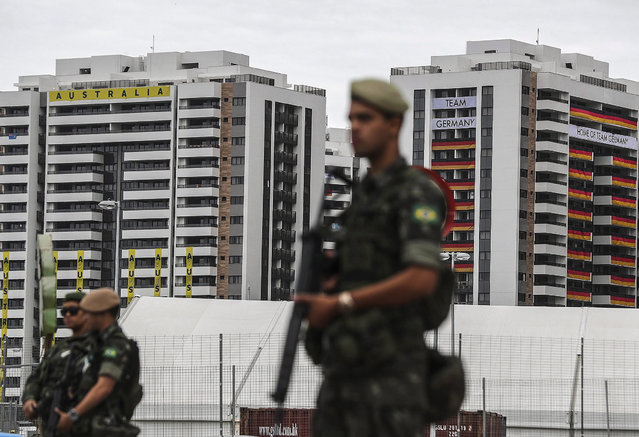 Members of the Brazilian Army stand guard outside the accommodation buildings of the delegations of Australia and Germany at Olympic Village in Rio de Janeiro, Brazil, 26 July 2016. The inauguration of the Olympic games of Rio 2016 will be officially held on 05 August. (Photo by Antonio Lacerda/EPA)