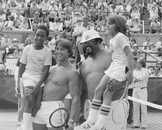 Actor and bodybuilder Arnold Schwarzenegger, second from left, and football player Rosey Grier, third from left, hold up their young opponents, left to right, Wesley Dixon, 10, and Robert Sanchez, 11, both of New Rochelle, at the RFK Celebrity Tennis Tournament in New York, Aug. 27, 1977. (Photo by Marty Lederhandler/AP Photo)