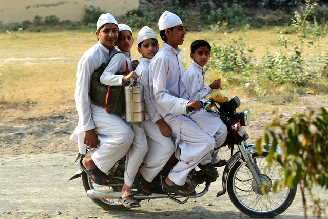 Four Pakistani brothers and a friend (L) crowd a motorcycle as they make their way home from school at a madrasa in Lahore on May 13, 2013. (Photo by Roberto Schmidt/AFP Photo)