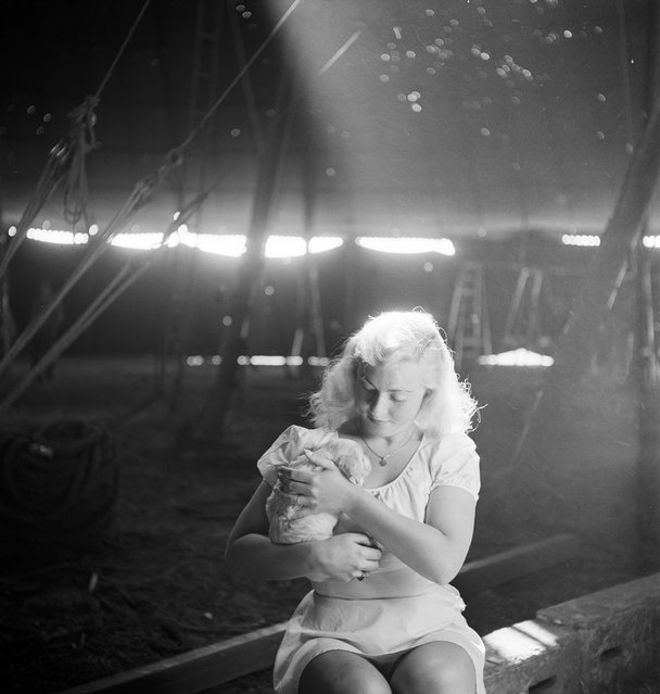 A picture of a circus girl sitting and holding a dog during a rehearsal for the Ringling Bros. and Barnum & Bailey Circus in Sarasota, FL in 1949. (Photo By Nina Leen/Time Life Pictures/Getty Images)