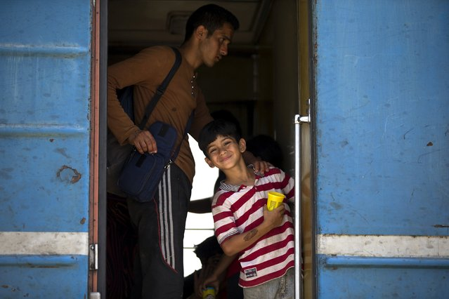A migrant boy smiles after boarding a train after crossing the Macedonian-Greek border near Gevgelija, Macedonia, September 6, 2015. (Photo by Stoyan Nenov/Reuters)