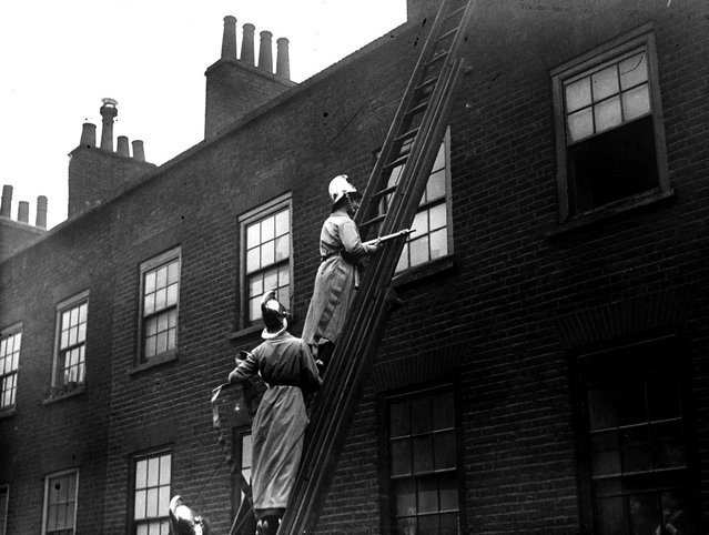 Members of the Women's Fire Brigade on a fire drill with hoses and extingushers at full force, March 1916. (Photo by Topical Press Agency)