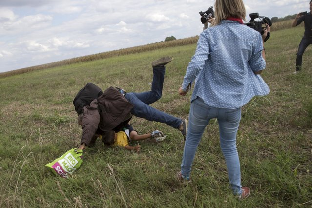 A migrant carrying a child falls after tripping on a TV camerawoman (R) while trying to escape from a collection point in Roszke village, Hungary, September 8, 2015. (Photo by Marko Djurica/Reuters)