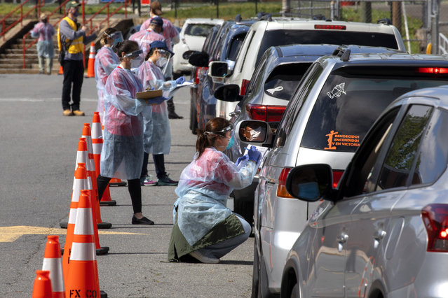 A man wearing a facemask waits inside his car to be tested for COVID-19 as volunteers take registration information in Annandale, Va., Saturday, May 23, 2020. COVID-19 testing was available from Fairfax County at no cost and without a doctor's order. Hundreds of people had lined up in cars and on foot by 10am. Officials planned on testing about 1000 people from 10 a.m. to 6 p.m. Testing will be available at Bailey's Elementary on Sunday. (Photo by Jacquelyn Martin/AP Photo)