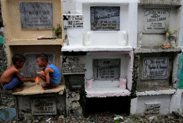 Children play in front of the apartment tombs during the observance of All Saints' Day at Navotas public cemetery in Metro Manila, Philippines, November 1, 2017. (Photo by Romeo Ranoco/Reuters)