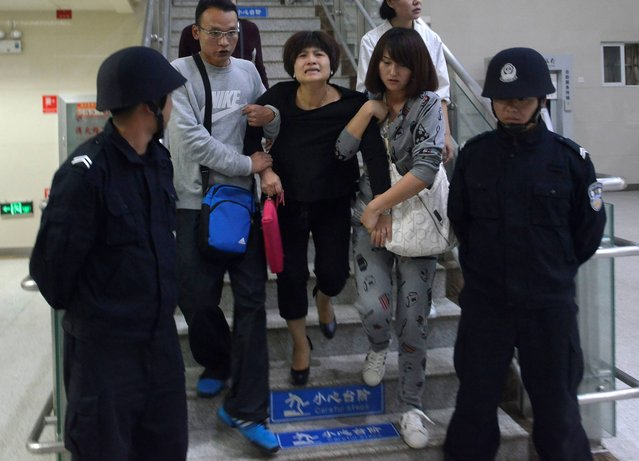 A woman, center, relative of a victim cries as she is helped down a staircase guarded by policemen at a hospital, after a stampede at Mingtong Primary School in Kunming in southwest China's Yunnan province Friday, September 26, 2014. Six schoolchildren died in the stampede, authorities said. It wasn't clear what caused the stampede among the first- and second-grade students of the primary school, the city's propaganda office said on its microblog. (Photo by AP Photo)