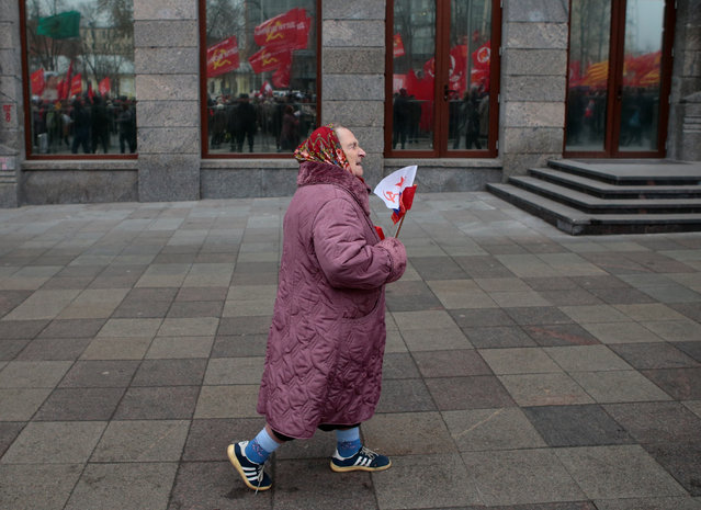 An elderly woman carries flags during a rally held by Russian Communist party to mark the Red October revolution's centenary in central Moscow, Russia on November 7, 2017. (Photo by Andrey Volkov/Reuters)