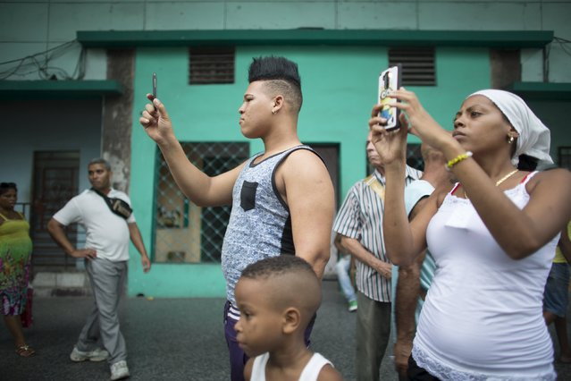 People take pictures during the annual procession of Our Lady of Charity, the patron saint of Cuba, on the streets of downtown Havana, September 8, 2015. (Photo by Alexandre Meneghini/Reuters)