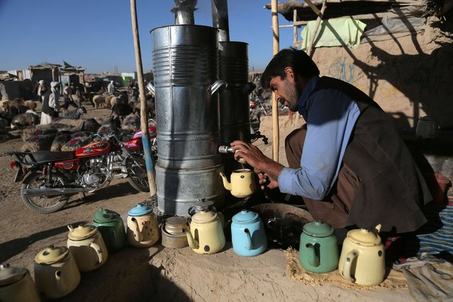 An Afghan man prepares tea for his customers at a livestock market ahead of the sacrificial Eid al-Adha festival in Ghazni on October 1, 2014. Muslims across the world are preparing to celebrate the annual festival of Eid al-Adha, or the Festival of Sacrifice, which marks the end of the Hajj pilgrimage to Mecca and commemorates Prophet Abraham's readiness to sacrifice his son to show obedience to God. (Photo by Rahmatullah Alizadah/AFP Photo)
