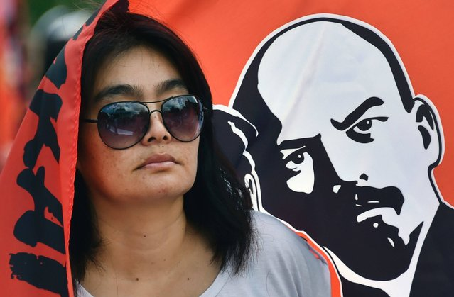 """A woman stands by a flag picturing Vladimir Lenin, the founder of the Union of Soviet Socialist Republics (USSR), during a rally in downtown Moscow on August 22, 2016, to mark the symbolic 25th anniversary of the August 1991 putsch. On August 19, 1991, a group of security chiefs and Communist bosses who opposed Mikhail Gorbachev's decentralising reforms declared themselves in charge, ushering in three days of turbulence. Calling themselves the State Committee for the State of the Emergency, they said Gorbachev had stepped aside for """"health reasons"""" and sent tanks rolling into the centre of Moscow. But crowds flocked to the White House parliament building to defend Boris Yeltsin, the president of the Russian republic of the USSR, who was then seen as a symbol of reform and democracy. (Photo by Alexander Nemenov/AFP Photo)"""