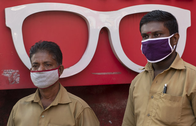 Auto rickshaw drivers wearing masks as a precaution against COVID-19 await customers near an optical shop in Kochi, Kerala state, India, Wednesday, June 24, 2020. India is the fourth hardest-hit country by the coronavirus in the world after the U.S., Russia and Brazil. (Photo by R.S. Iyer/AP Photo)