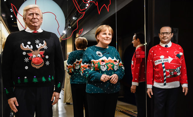 The wax figures of US President Donald Trump, German Chancellor Angela Merkel and former French President Francois Hollande are pictured in Christmas- themed sweaters at the Grevin Wax Museum on December 1, 2017 in Paris. (Photo by Bertrand Guay/AFP Photo)