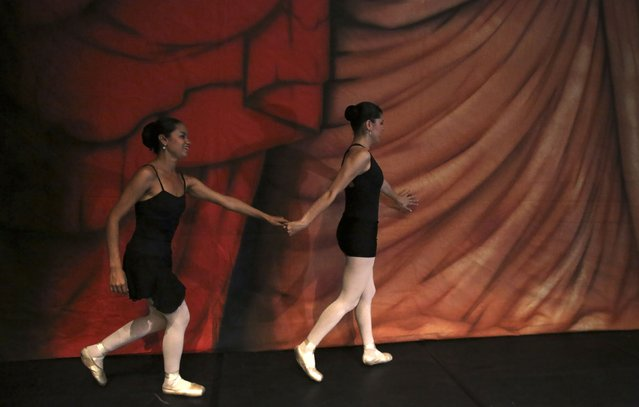 """Blind ballet students Aldenir (L) and Aldenice walk on the stage before performing """"Corsario' e Paquitas"""" during celebrations marking Brazil's Children's Day at the Italo Theater in Sao Paulo October 12, 2014. The Association was founded by Brazilian ballerina and physiotherapist Fernanda Bianchini in 1995, when she decided to teach classical ballet to the blind for free. (Photo by Nacho Doce/Reuters)"""