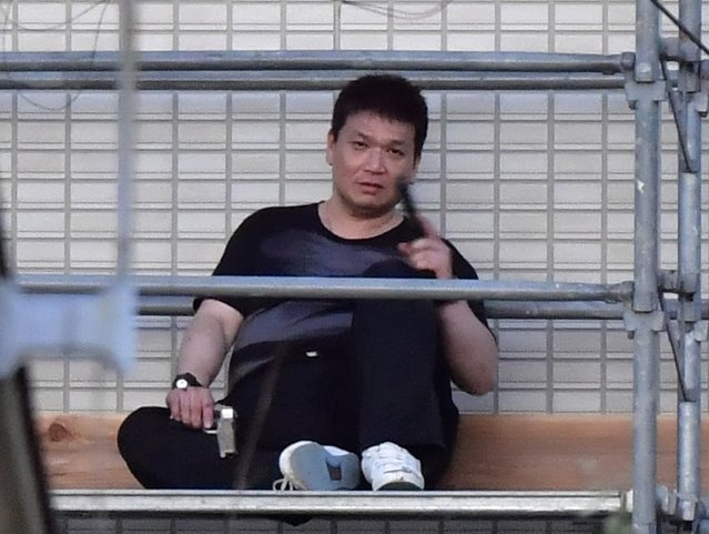 Yasuhide Mizobata, a murder suspect, holding guns sits on scaffoldings as he holes up at an apartment in a standoff after he fired at a police car and escaped, in Wakayama, central Japan, Wednesday, August 31, 2016. Wakayama police said Wednesday that Mizobata, 45, is wanted as prime suspect in a shooting Monday at a small construction company, where he allegedly shot one employee dead and left three others injured. (Photo by Ren Onuma/Kyodo News via AP Photo)
