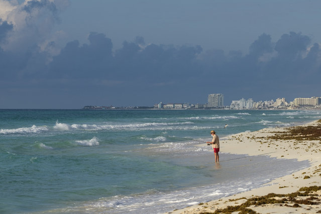 A tourist fishes from the shore in Cancun, Mexico, Thursday, June 11, 2020. An irony of the coronavirus pandemic is that the idyllic beach vacation in Mexico in the brochures really does exist now: the white sand beaches are sparkling clean and empty on the Caribbean coast. (Photo by Victor Ruiz/AP Photo)