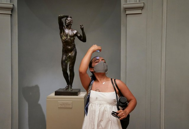 Mariana Martinez of Arlington, Virginia, imitates a statue while making a birthday visit to the West Building of the National Gallery of Art, which reopened after months of closure due to the outbreak, in Washington, July 20, 2020. (Photo by Kevin Lamarque/Reuters)