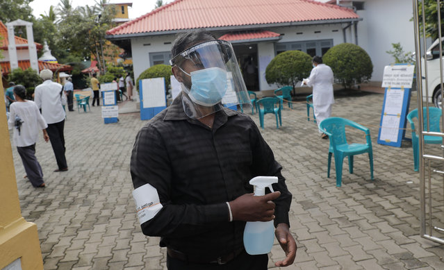 A Sri Lankan polling officer wearing mask and face shield stands holding a sanitizer sprayer at the entrance to a polling center during the parliamentary election in Colombo, Sri Lanka, Wednesday, August 5, 2020. The election was originally scheduled for April but was twice postponed due to the COVID-19 pandemic. (Photo by Eranga Jayawardena/AP Photo)