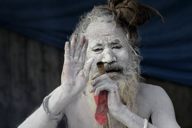 A sadhu, or a Hindu holy man, blesses a devotee as he smokes marijuana at a transit camp on the way to Gangasagar, in Kolkata, India, Sunday, January 7, 2018. Thousands of Hindu pilgrims are expected to take the annual holy dip at Gangasagar, where the Ganges River reaches the Bay of Bengal, on the auspicious Makar Sankranti festival day that falls on Jan. 14. (Photo by Bikas Das/AP Photo)