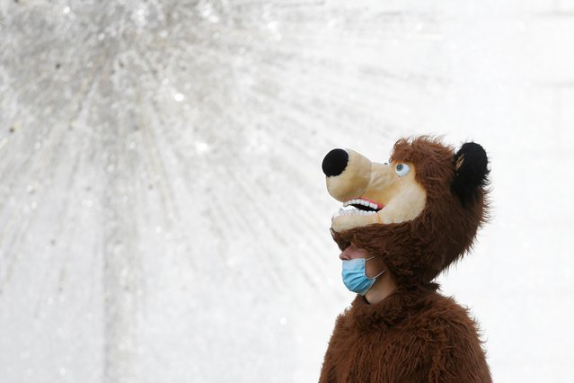 A man dressed as a bear and wearing a protective face mask amid the outbreak of the coronavirus disease (COVID-19) stands in front of a fountain in central Kyiv, Ukraine on August 11, 2020. (Photo by Valentyn Ogirenko/Reuters)