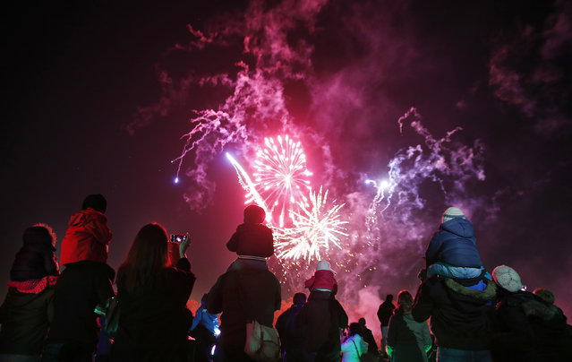 "Children sit on their parents' shoulders as they watch a bonfire night firework display at Roundwood Park in northwest London November 5, 2014. The fireworks display is one of many across the country which marks the uncovering of Guy Fawkes' ""Gunpowder Plot"" to blow up the Houses of Parliament in 1605. (Photo by Suzanne Plunkett/Reuters)"