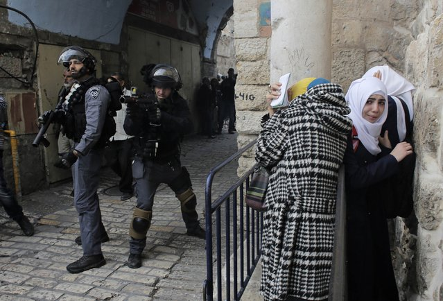 Palestinian women take cover as Israeli police used stun grenades to disperse a crowd trying to enter the compound known to Muslims as Noble Sanctuary and to Jews as Temple Mount  in Jerusalem's Old City November 5, 2014. Israeli security forces entered the Jerusalem holy compound and clashed with Palestinian stone throwers on Wednesday, officials said. (Photo by Ammar Awad/Reuters)